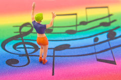 Listen to the music. Miniature woman on colorful music background Stock Images