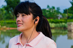 Listen to music of Asian women Stock Photo