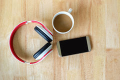 Listen to music from smart phone and drink hot coffee. Top view of headphone, smart phone and a cup of hot coffee on wood background Royalty Free Stock Image