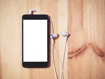 Listen to music. vertical smartphone with black case and a blank white screen and headphones with a ear on the wooden surface royalty free stock image