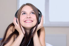 Listen to music. Young woman with ear buds in white lying in bed holding mp3 player Stock Images