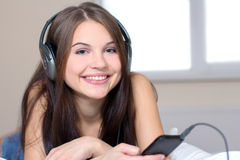 Listen to music. Young woman with ear buds in white lying in bed holding mp3 player Royalty Free Stock Photo