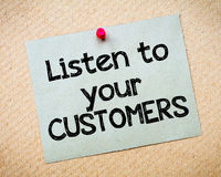 Listen to your customers. Message. Recycled paper note pinned on cork board. Concept Image Stock Photo