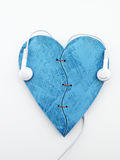 Listen to your heart. Two pieces of blue heart with white headphones Royalty Free Stock Images
