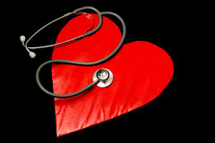 Listen to your heart. Red heart on black background with stethoscope on top Stock Photography