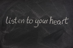 Listen to your heart on a blackboard Royalty Free Stock Photography