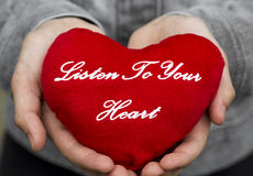 Listen to your heart. Plush heart with an inscription in the hands Listen to your heart Royalty Free Stock Photo