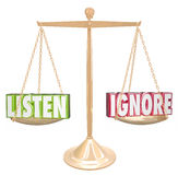 Listen Vs Ignore 3d Words Gold Scale Balance. Listen and Ignore words in 3d letters on a gold metal scale or balance weighing options to pay attention or avoid Stock Photography