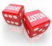 Listen Vs Ignore 2 Red Dice Words Paying Attention. Listen and Ignore words on two red 3d dice to illustrate the choice to pay attention or avoid listening to a Stock Photography