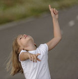 Listen. A young girl pointing to the sky with a listen gesture Royalty Free Stock Photos