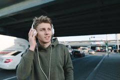 Listened to music by the man in the headphones against the backdrop of urban scenery, roads and cars. Lifestyle and people concept royalty free stock image