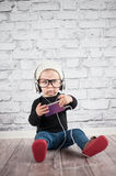 Listener. Cute baby girl with mp3 player Stock Photo