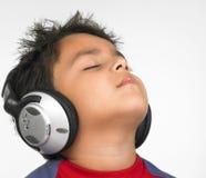 Listenig asiático do menino à música Fotografia de Stock Royalty Free