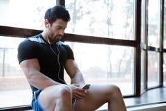 Listenin de sportif en musique, utilisant son téléphone portable se reposant sur le windowcill Photo stock
