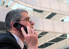 Listening. Man speaking to the phone in front of a modern building Stock Photo