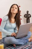 Listening. Young lady with long dark brown hair, blue top, jeans and laptop, sitting on the floor of her living room Royalty Free Stock Photography