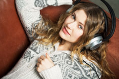 Listening. Young woman listening to music on the couch and relax while Stock Image