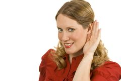Listening. Young woman on white holding hand to ear listening Royalty Free Stock Photos