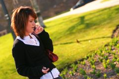 Listening. Concerned woman listening to a caller on her cell phone in the park stock photography