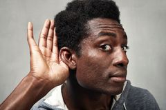 Listening black man. Hand behind ear of hearing eavesdropping man. Deaf people royalty free stock photos