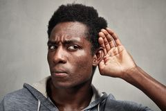 Listening black man. Hand behind ear of hearing eavesdropping man. Deaf people royalty free stock photo