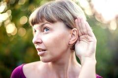 listening Ciérrese encima a mano de la mujer y del oído que están atento un s reservado fotografía de archivo libre de regalías