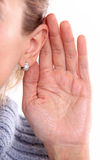 Listening: closeup view of female hand on her ear. Over white background stock images