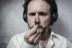 Listening and enjoying music with headphones, man in white shirt Stock Image