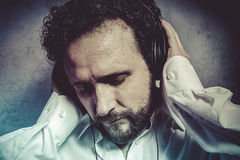 Listening and enjoying music with headphones, man in white shirt Stock Photos