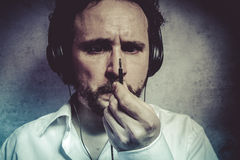Listening and enjoying music with headphones, man in white shirt Stock Images
