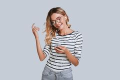 Listening her favorite song. Attractive young woman smiling and gesturing while standing against grey background stock photos