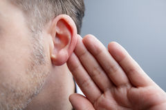 Listening. Man with hand on ear listening for quiet sound or paying attention Royalty Free Stock Photos