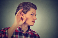Listening man holds with hand to ear gesture Royalty Free Stock Images