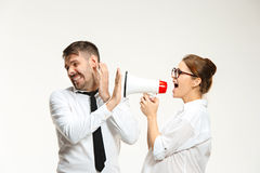 Listening, Megaphone, Shouting. Successful business couple at the office on white background. Listening, Megaphone, Shouting concept Royalty Free Stock Photo