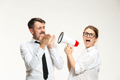 Listening, Megaphone, Shouting. Successful business couple at the office on white background. Listening, Megaphone, Shouting concept Royalty Free Stock Image