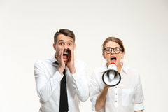 Listening, Megaphone, Shouting. Successful business couple at the office on white background. Listening, Megaphone, Shouting concept Stock Photos