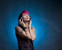 Listening music. Tattooed girl listening music on headphones Stock Image