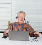 Listening music. Senior man listen music from laptop and make some rap movements Royalty Free Stock Image