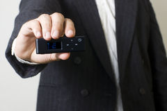 Listening music. Man with suit listening music from a mp3 player Royalty Free Stock Photo
