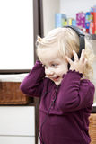Listening the music  - baby girl with headphone Stock Photos