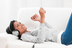 Listening music at home. Young beautiful woman listening music while relaxing on sofa at home Stock Image