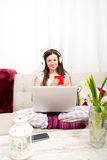 Listening music at home with the laptop. Young woman relax listening some music at home with the laptop Stock Photography