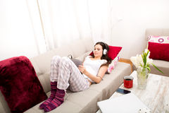 Listening music at home with the tablet. Young woman relax listening some music at home with the tablet Royalty Free Stock Photography