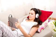 Listening music at home. Young woman relax listening some music at home Royalty Free Stock Photo