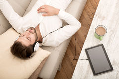 Listening music on the Sofa. A young Hipster styled man listening music on the sofa with headphones Royalty Free Stock Image