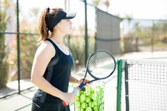 Listening music after tennis practice. Side view of a young hispanic female tennis player with racket listening to songs on her earbuds after tennis training Stock Photo
