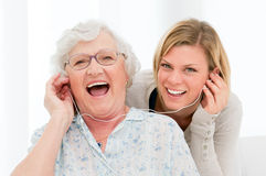 Listening music together. Super happy and excited grandmother listening music with her granddaughter at home Stock Photos