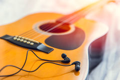 Listening and play the music with guitar, relax happy time with song concept. Closeup wood folk guitar with earplug headphone Royalty Free Stock Photo