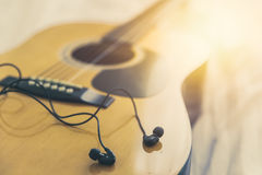 Listening and play the music with guitar, relax happy time with song concept. Closeup wood folk guitar with earplug headphone vintage color tone Royalty Free Stock Photo