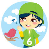 Listening the Songbird. Young boy with green baseball cap listening a cute little bird singing Royalty Free Stock Photo